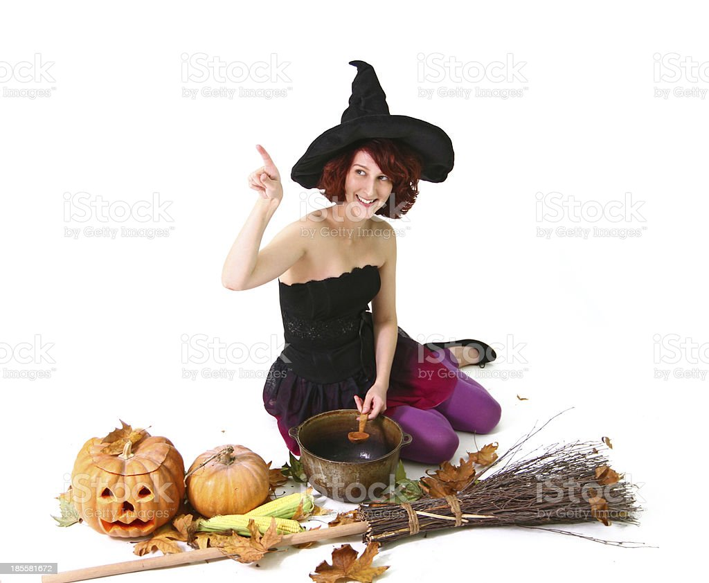 Halloween witch with pumpkin, leaves, broom, spoon,  corn and pot stock photo