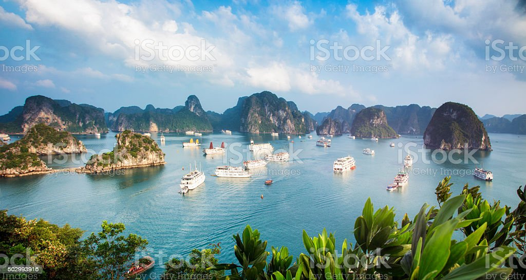 Halong Bay Vietnam panorama at sunset with anchored ships stock photo