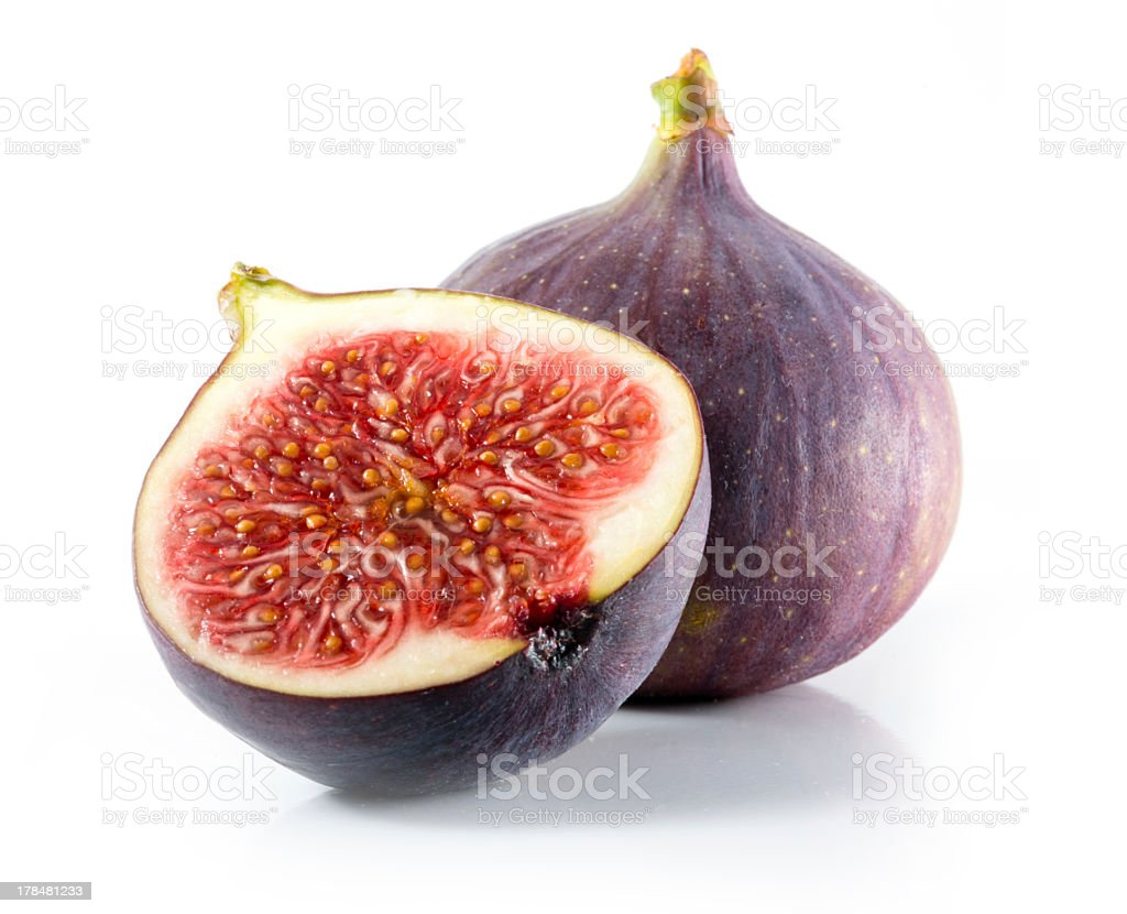 A halved and whole fig isolated on a white background stock photo