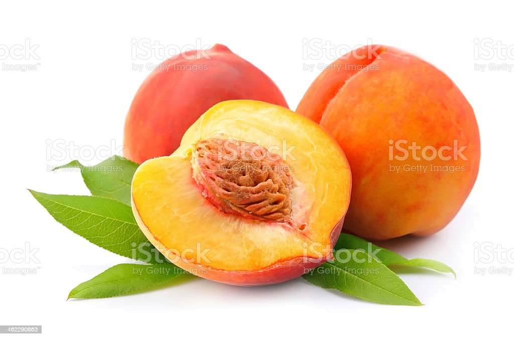 A halved and whole peaches with leaves isolated on white stock photo