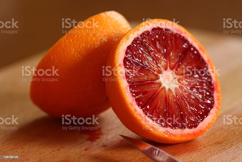 Halved blood orange on a wood table with a knife blade stock photo