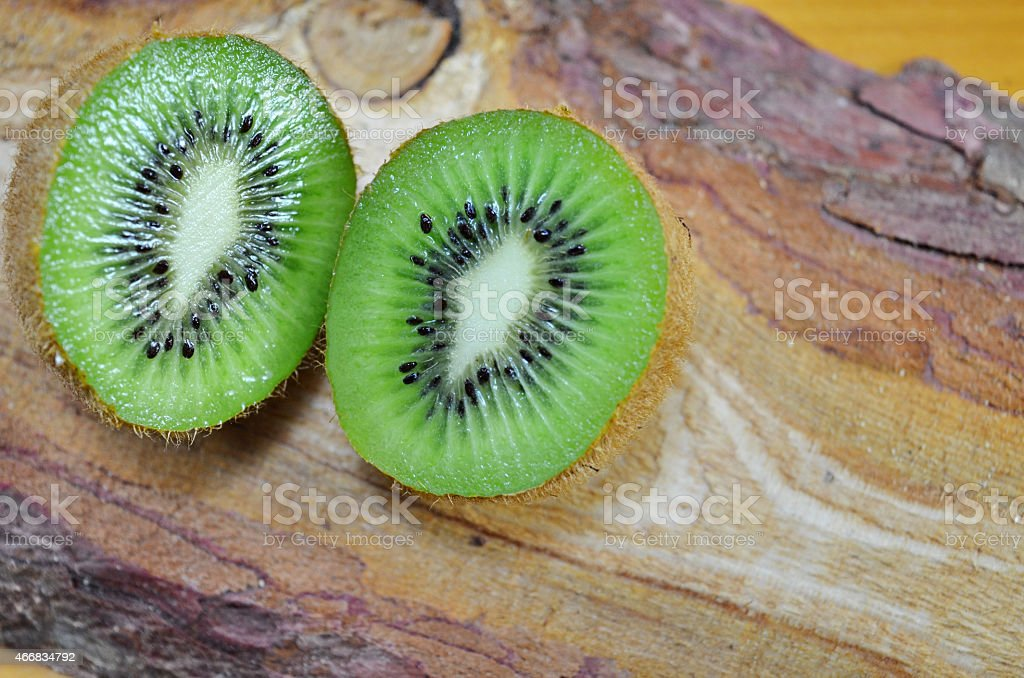 Halved kiwi on a wooden table royalty-free stock photo