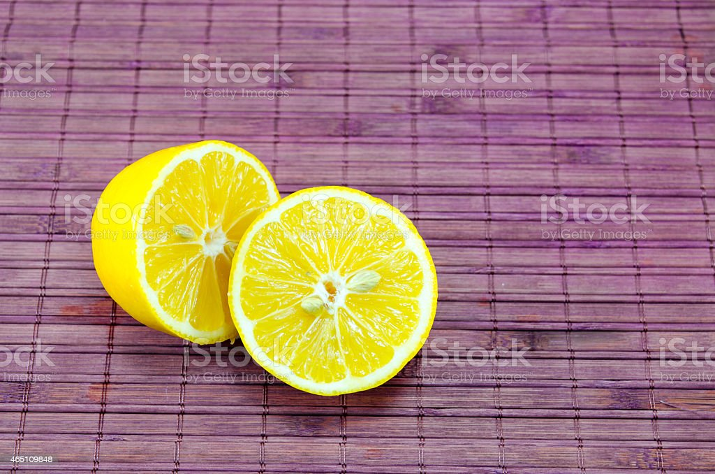 Halved lemons on a bamboo surface royalty-free stock photo