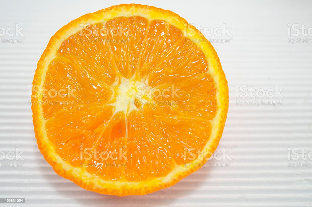 Halved orange on a white cardboard close up royalty-free stock photo