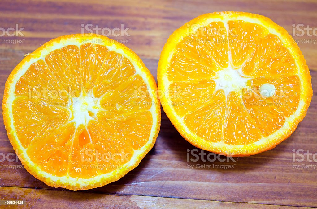 Halved orange on a wooden table close up royalty-free stock photo