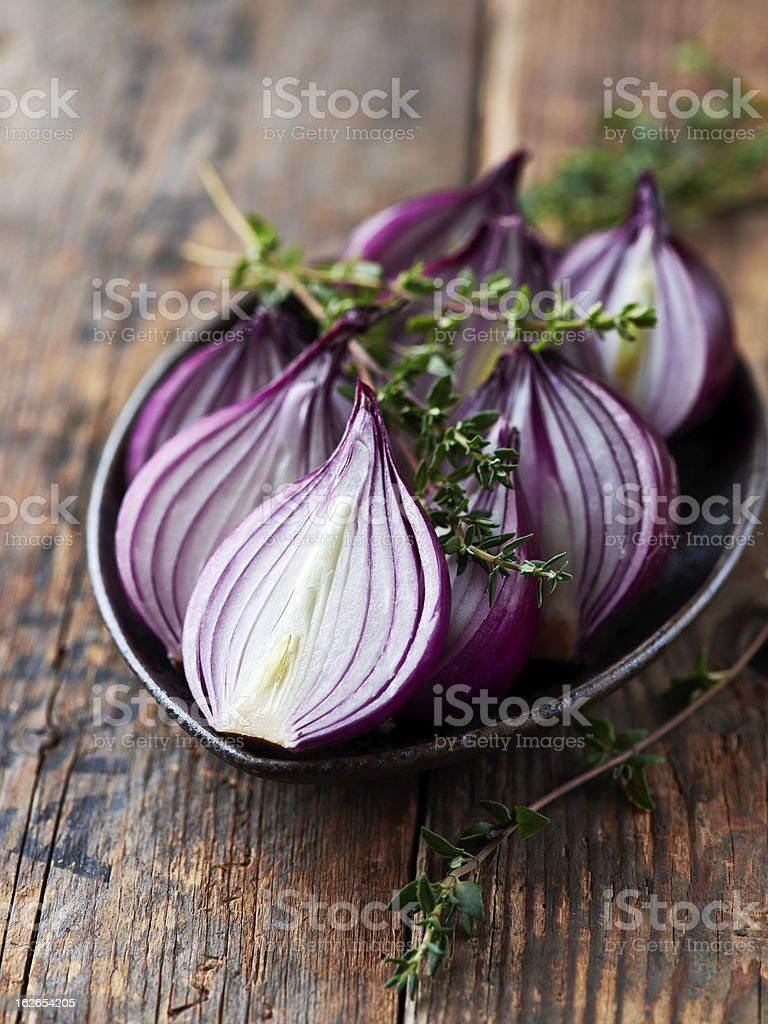 Halved red onions with thyme stock photo
