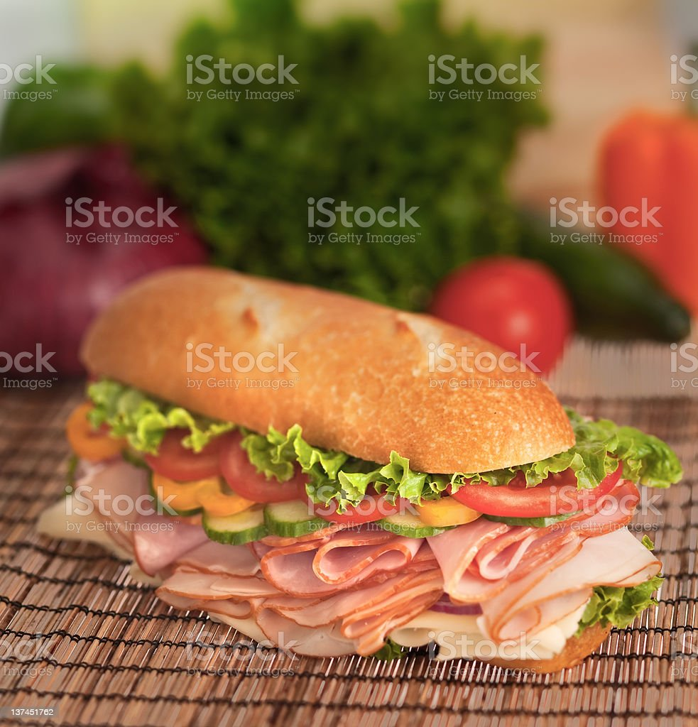 Ham & turkey sandwich with fresh produce in the background royalty-free stock photo