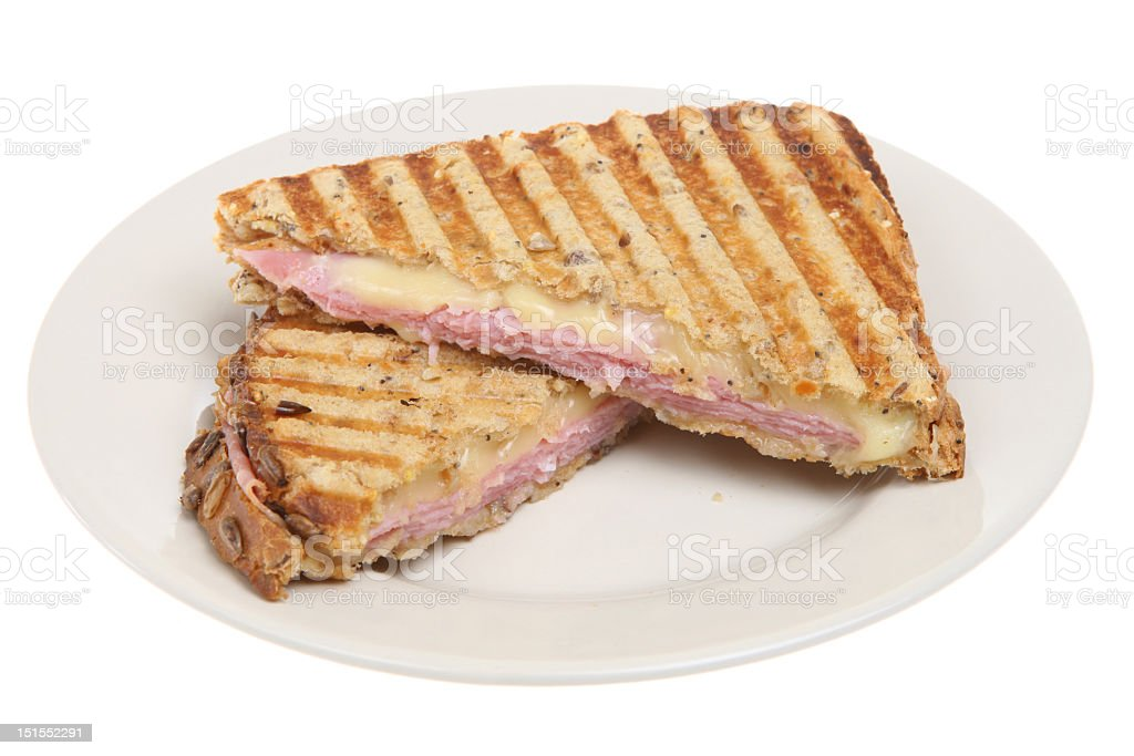 A ham and cheese panini served on a white plate stock photo