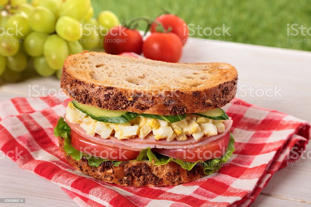 Ham and egg picnic sandwich on summer outdoor table stock photo