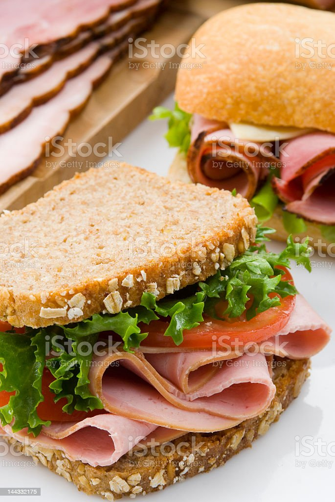 Ham and salad sandwich on white table stock photo