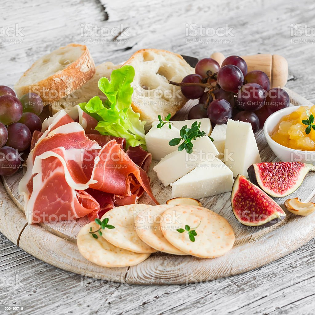 Ham, cheese, grapes, figs, ciabatta, cracker, jam on wooden board stock photo