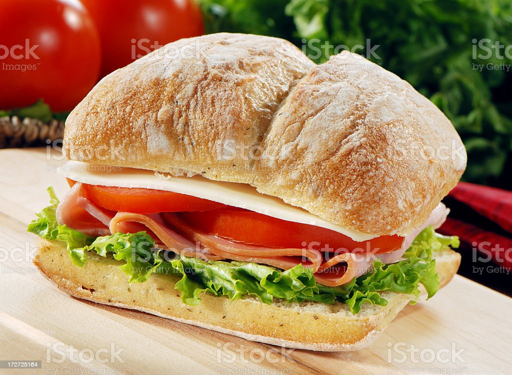 Ham lettuce tomato and provolone on a fresh baguette stock photo
