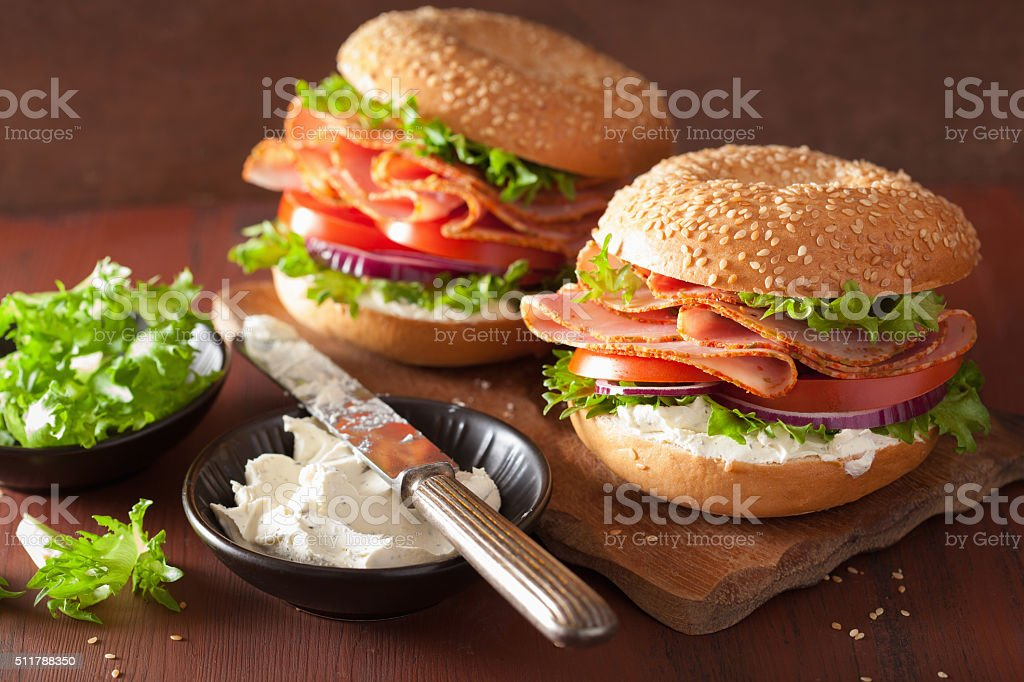 ham sandwich on bagel with cream cheese tomato onion stock photo