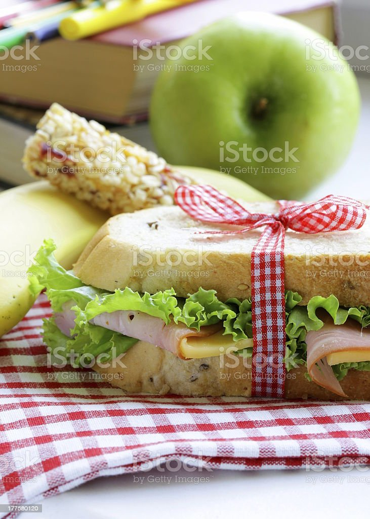 Ham sandwich tied in ribbon with an apple, banana and a bar royalty-free stock photo
