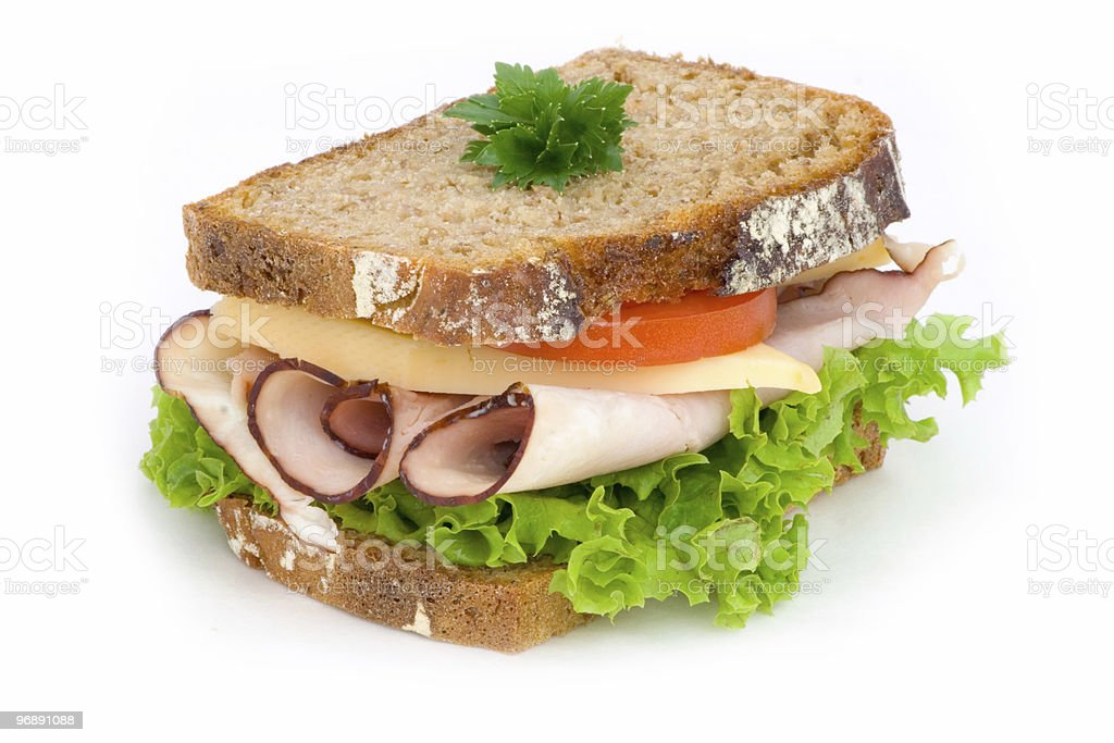 A ham sandwich with lettuce and tomato on wheat bread royalty-free stock photo