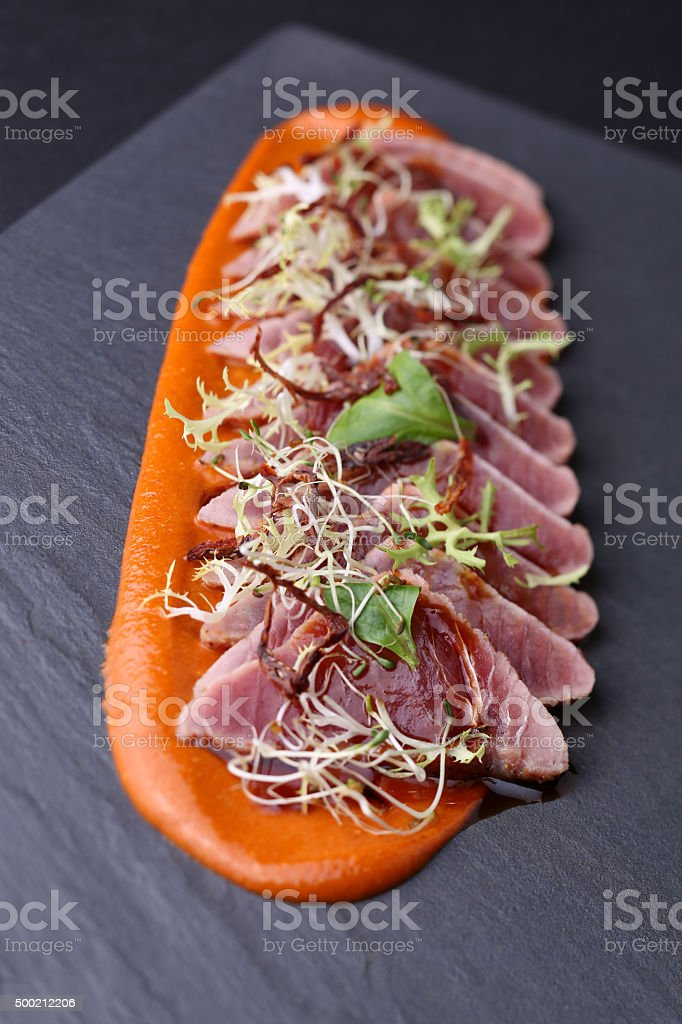 Ham with arugula, microgreen and the carrot sauce on dark stock photo