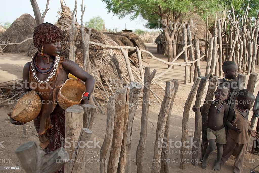Hamar woman passes by Karo kids, Colcho, Omo Valley, Ethiopia. stock photo