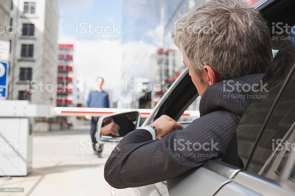 Hamburg, Businessman sitting in car in front of closed barrier stock photo