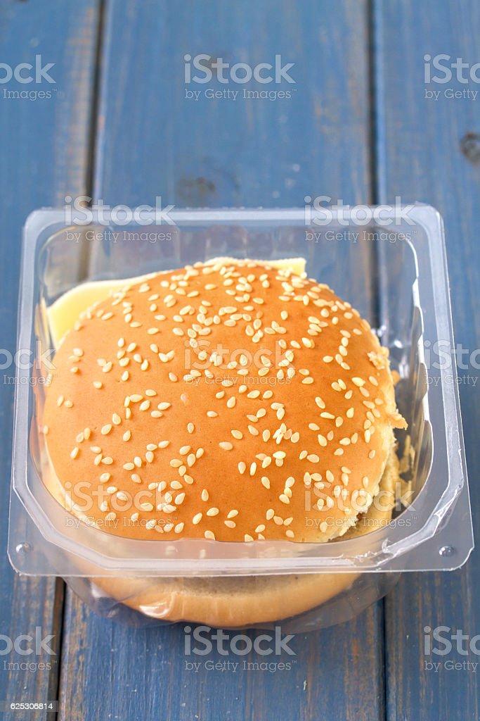 hamburger in plastic box on blue wooden background stock photo