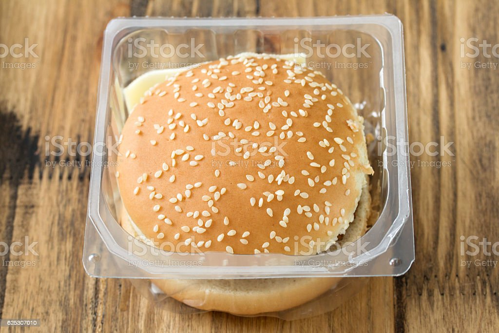 hamburger in plastic box on brown wooden background stock photo