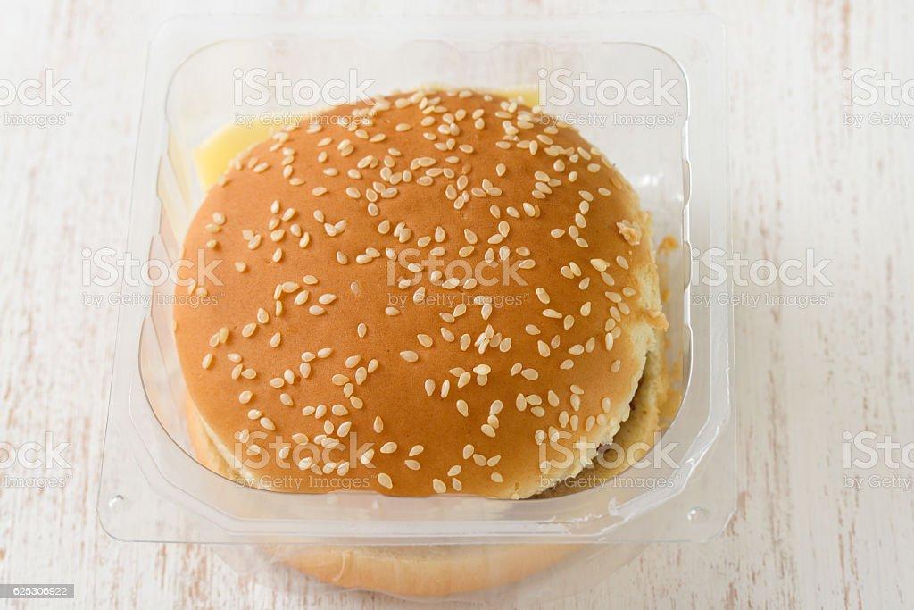 hamburger in plastic box on white wooden background stock photo