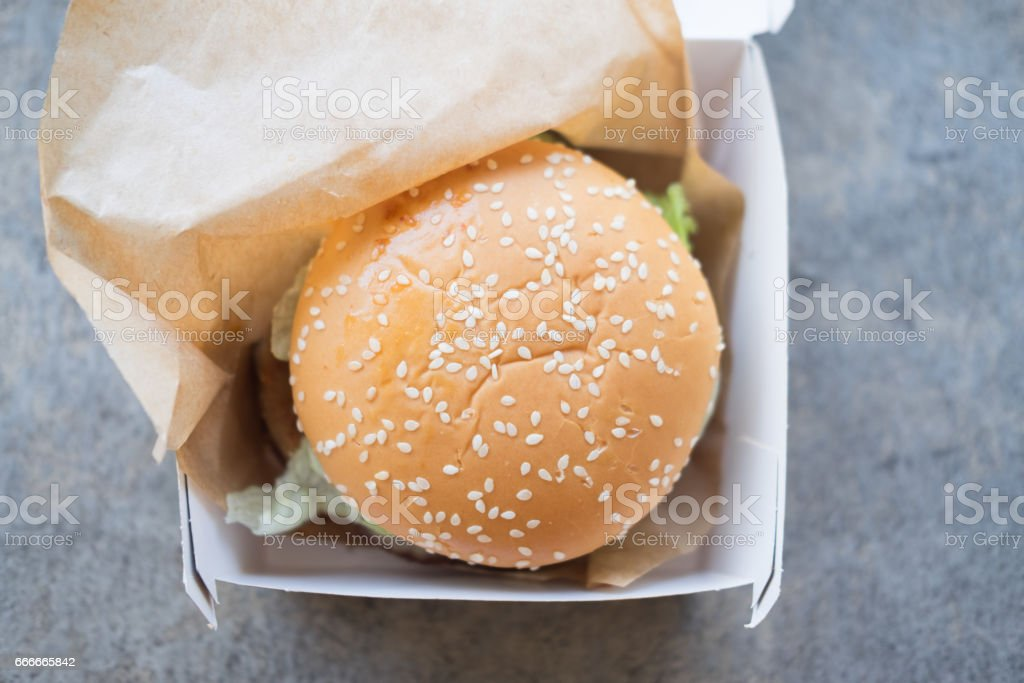 Hamburger is a fast food make from bun meat cheese and vegetable in white paper box stock photo