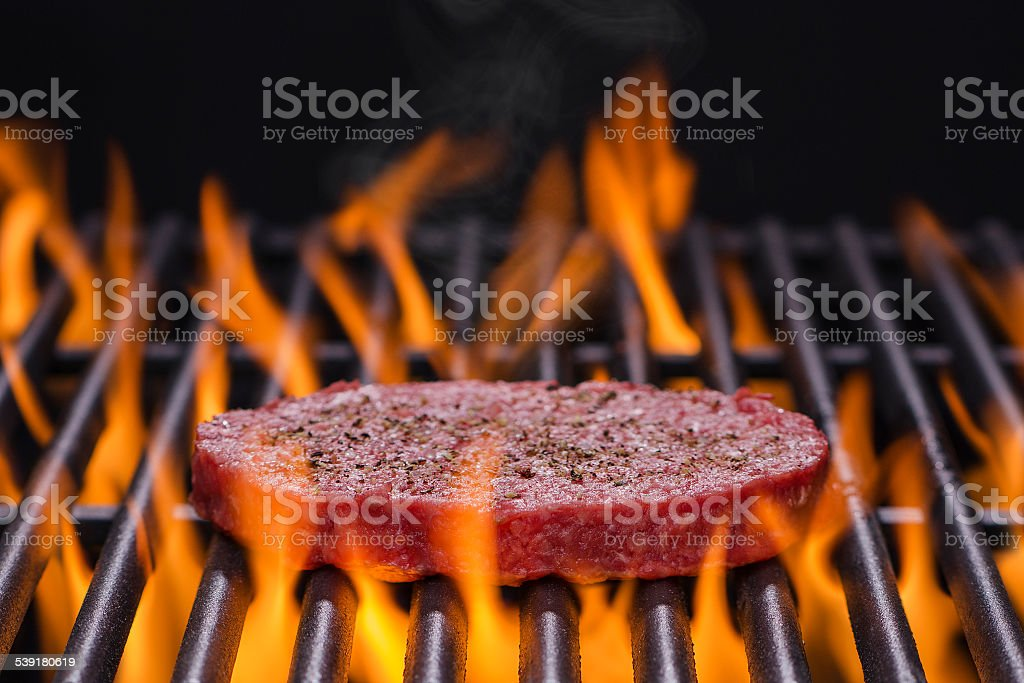 Hamburger on a Hot Flaming Grill stock photo