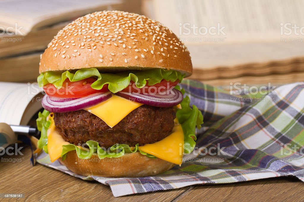 hamburger on a napkin. Background of notebooks and textbooks stock photo
