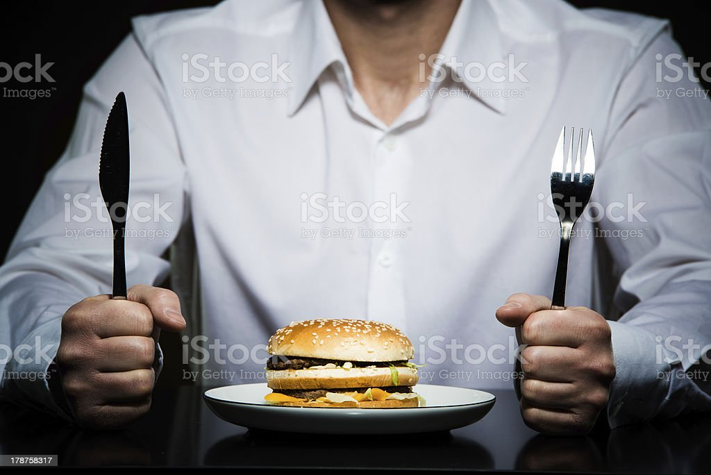 hamburger on a plate in front of  man stock photo