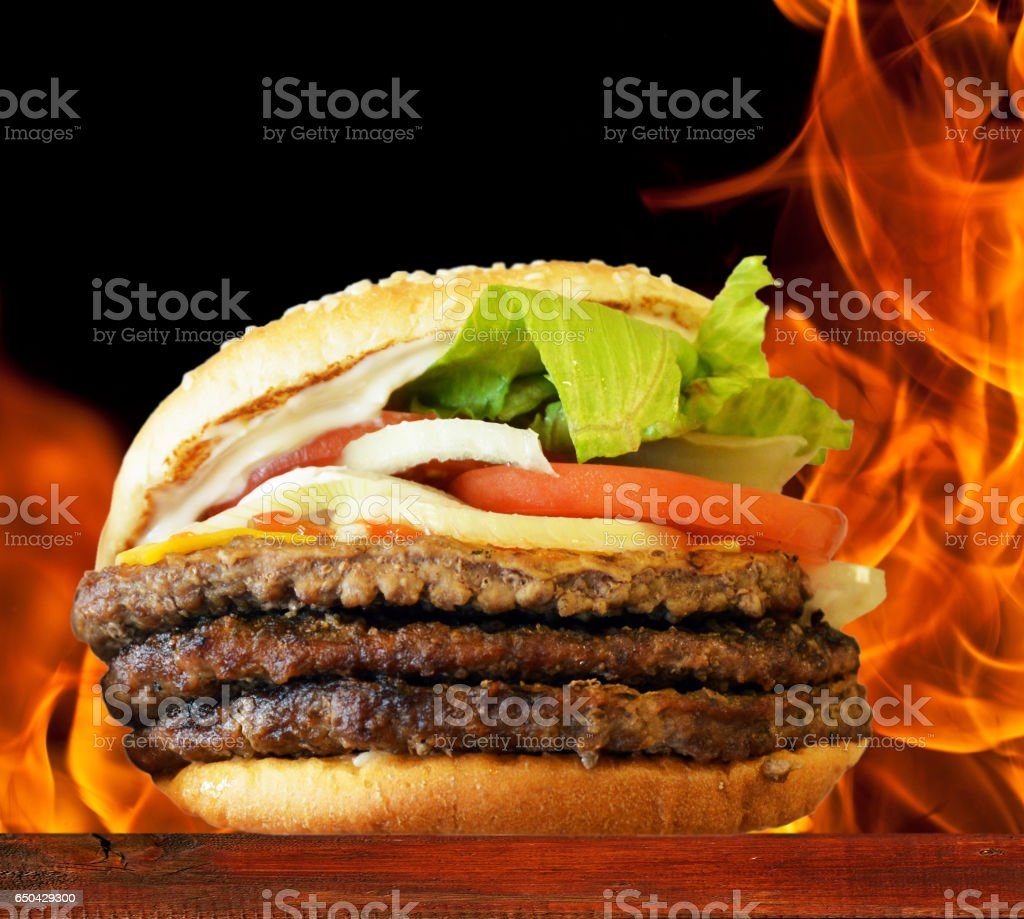 Hamburger on wooden plate against flame background stock photo