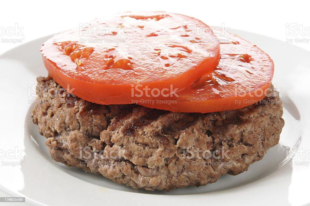 Hamburger patty with sliced tomato royalty-free stock photo