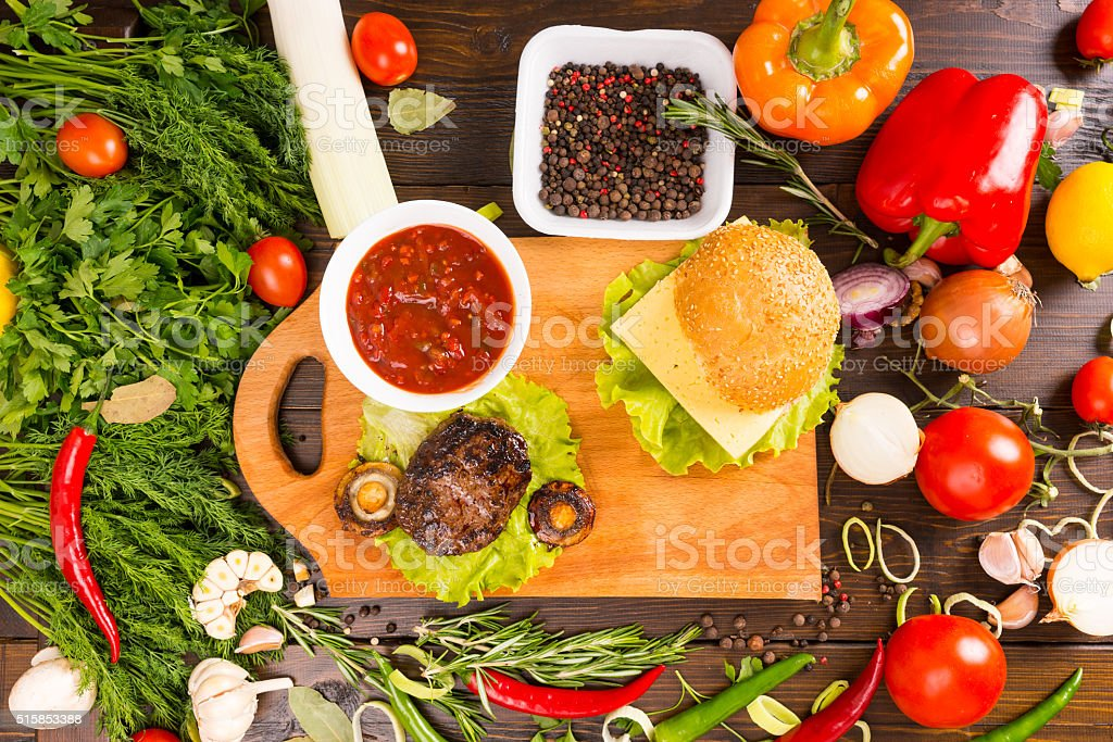 Hamburger Surrounded by Fresh Veggies and Toppings stock photo