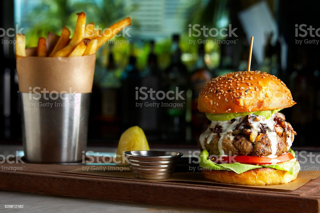 Hamburger with blue cheese, avocado and fries stock photo