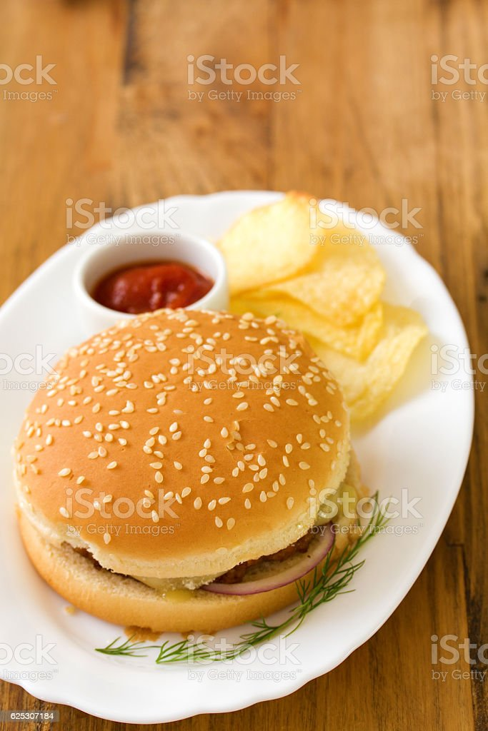 hamburger with chips and sauce on dish stock photo