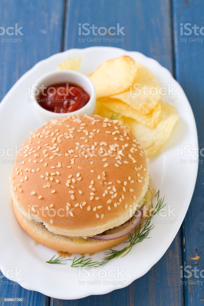 hamburger with chips and tomato sauce on dish stock photo