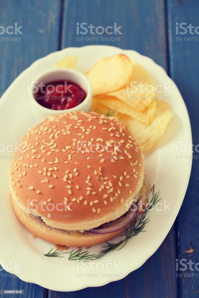 hamburger with chips and tomato sauce on white dish stock photo