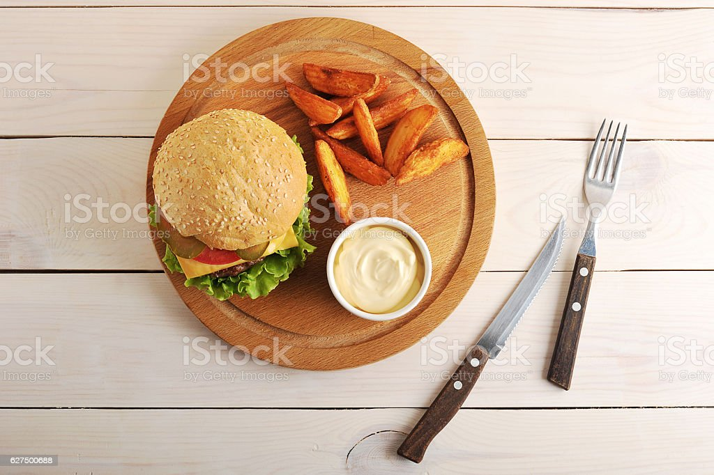 hamburger with Idaho potatoes and cheese sauce on a round stock photo