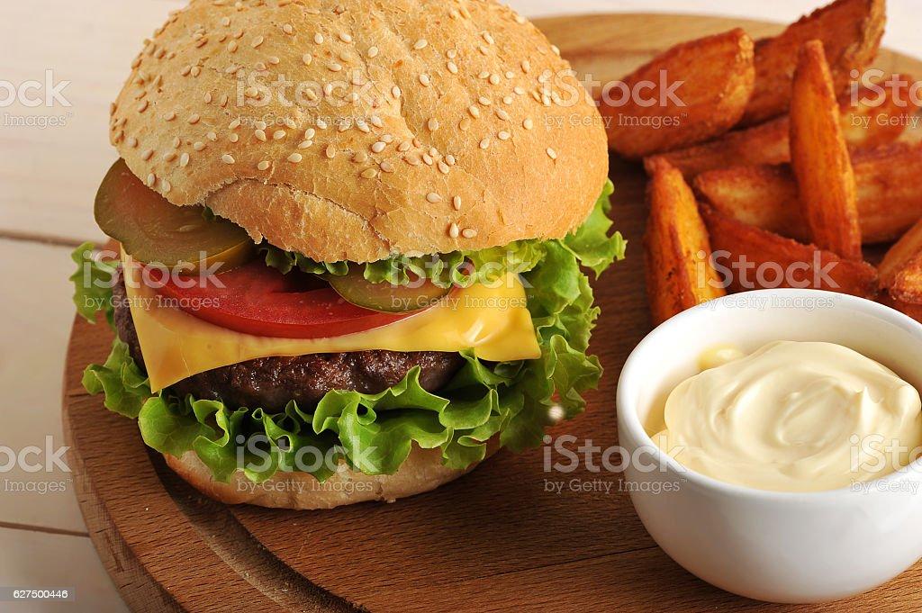 hamburger with Idaho potatoes and cheese sauce stock photo