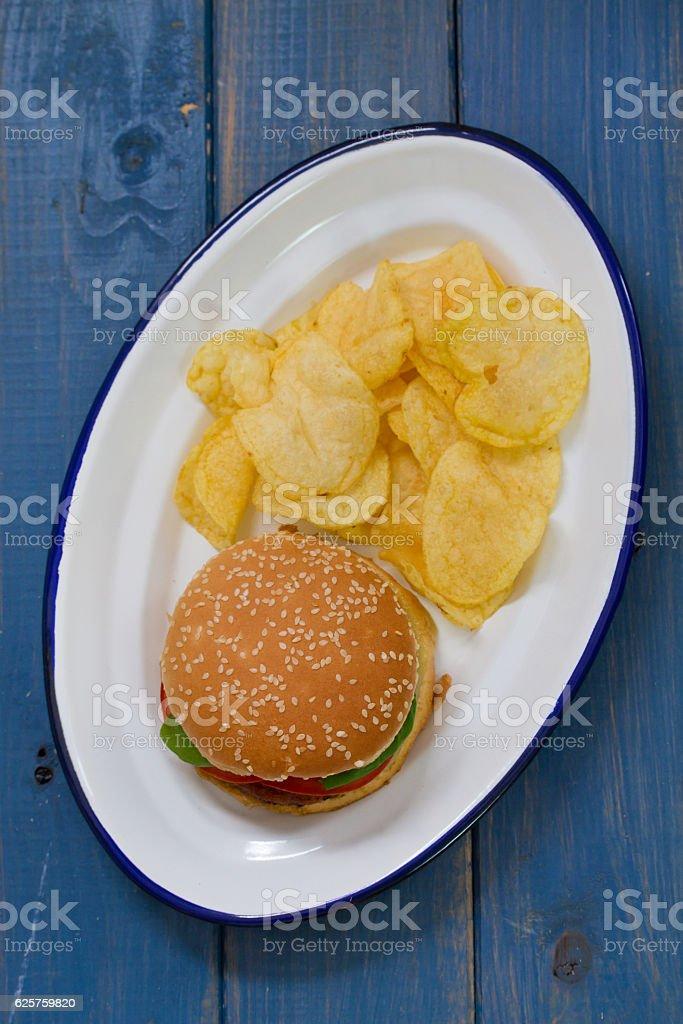 hamburger with potato chips on white dish on blue background stock photo