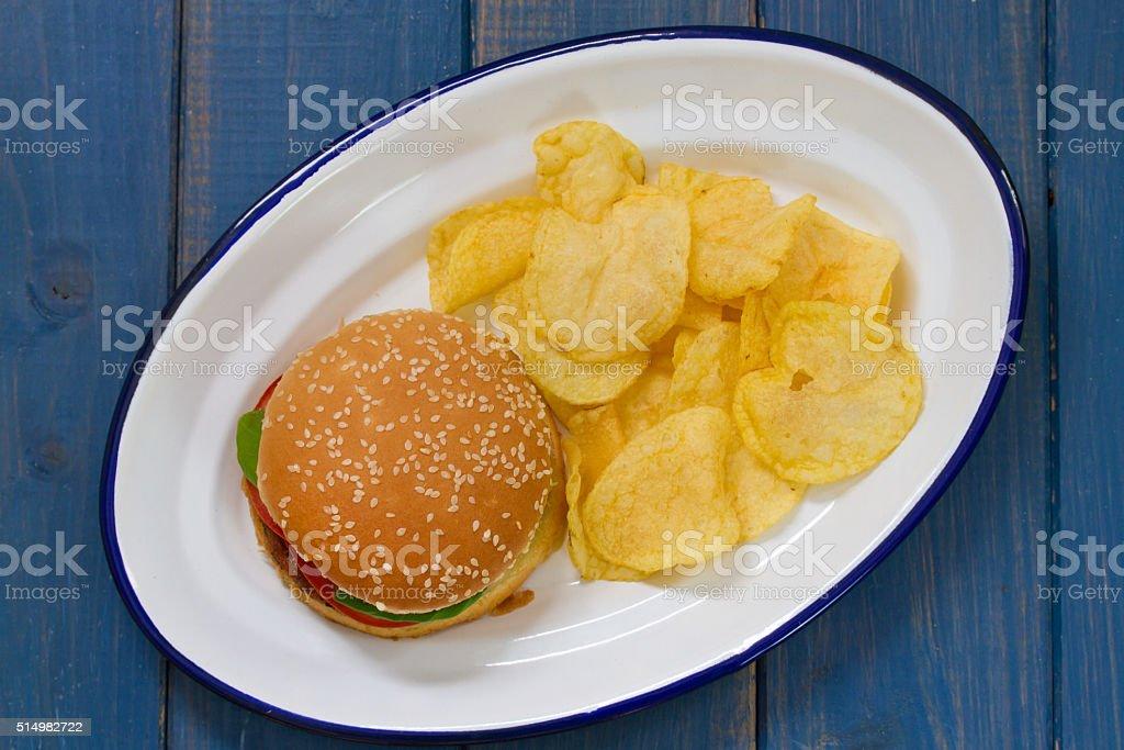 hamburger with potato chips on white dish stock photo