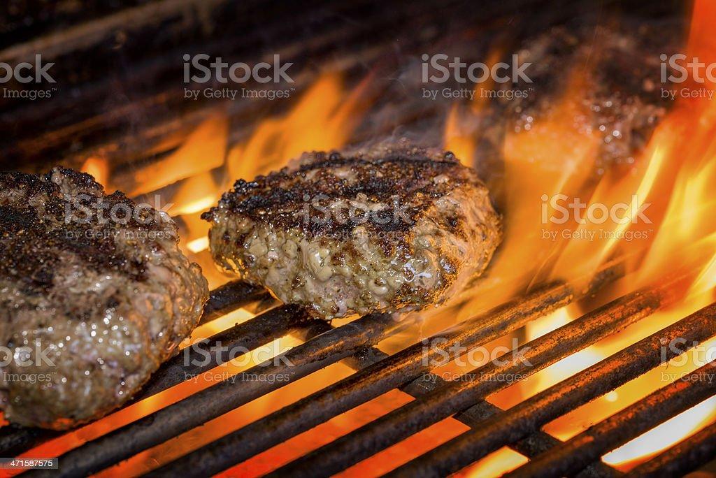 Hamburgers on a Flaming Grill stock photo
