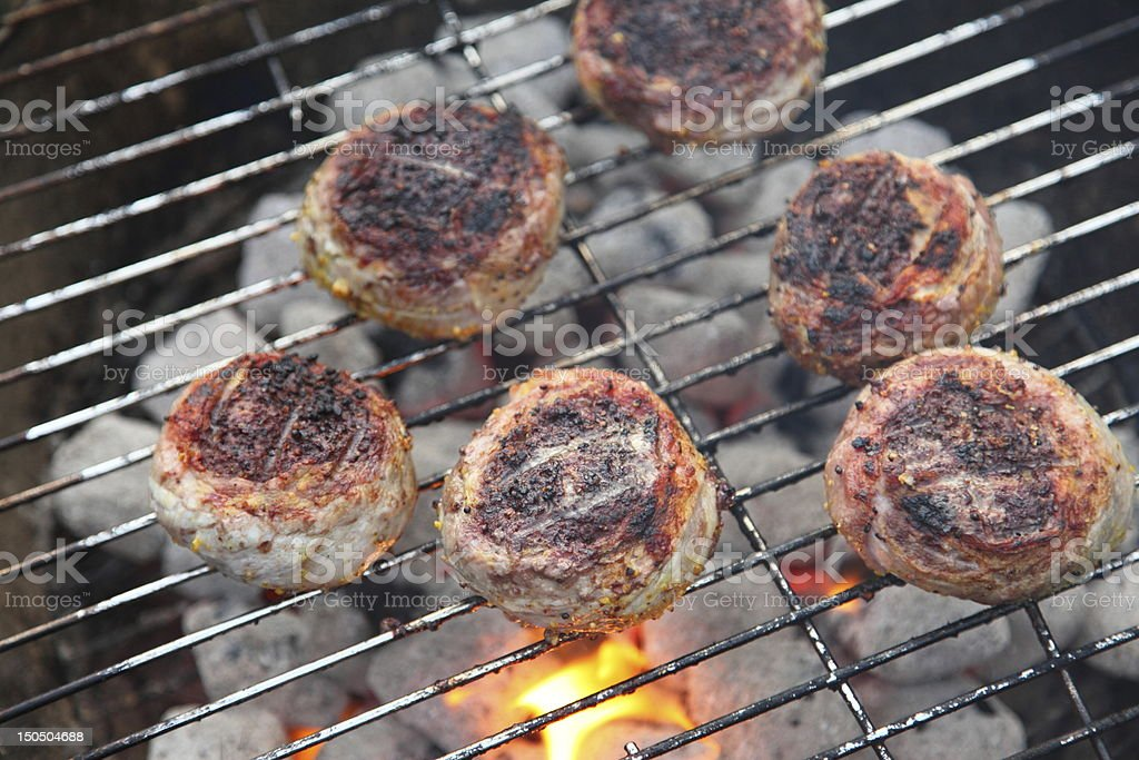 Hamburgers with bacon wrap on barbecue stock photo