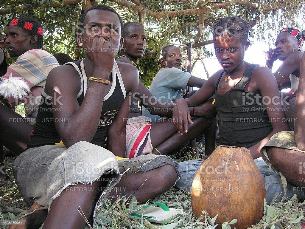 Hamer men drink traditional beer in Omo Valley, Ethiopia. stock photo