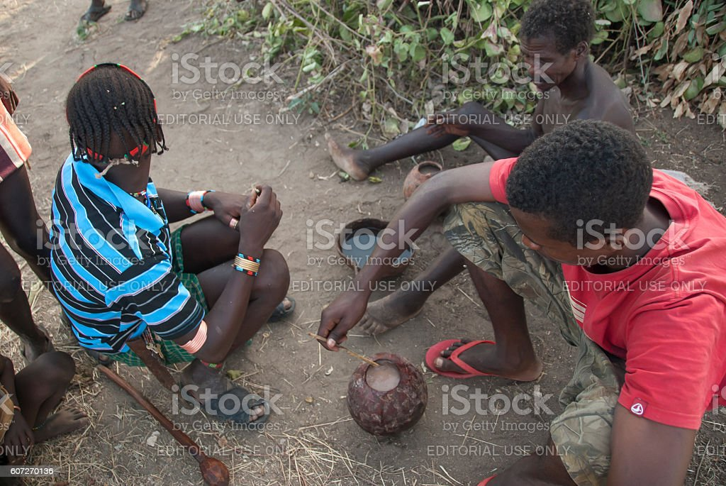 Hamer men drink traditional beer near Dimeka,Omo Valley, Ethiopia. stock photo