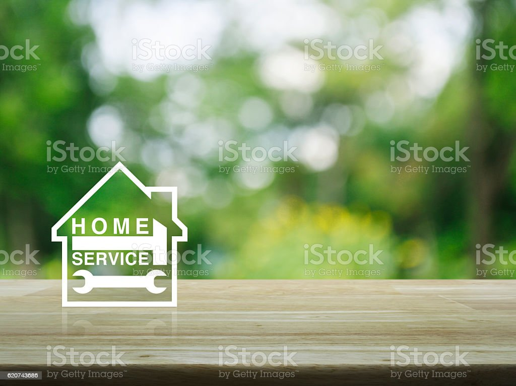 Hammer and wrench with house icon on table over tree stock photo