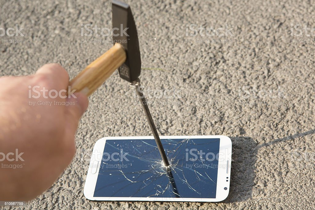 hammer smashing the screen of a smartphone stock photo