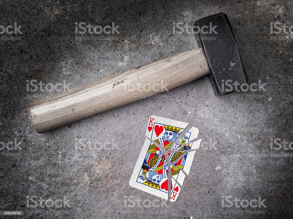 Hammer with a broken card, king of hearts stock photo