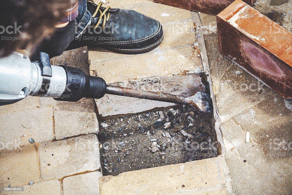 Hammer with  flat spade destroys masonry stock photo