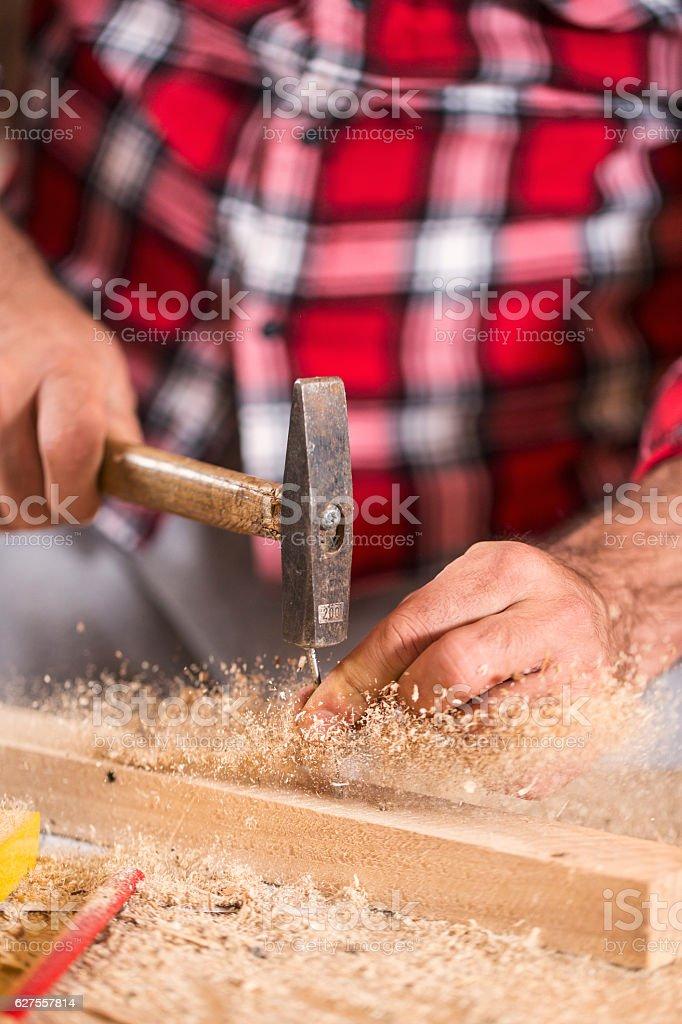 Hammering a nail into wooden board. Close up royalty-free stock photo