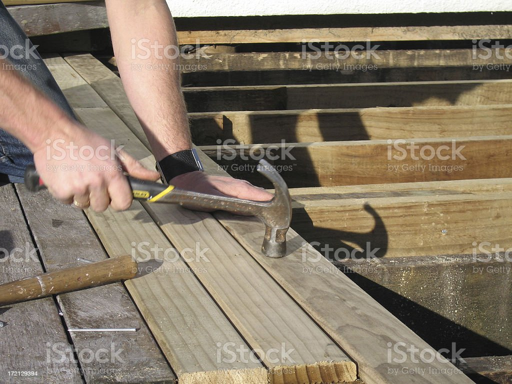 Hammering nails into deck royalty-free stock photo